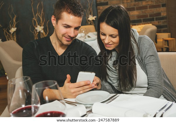 Close up portrait of attractive couple looking at smart phone at restaurant
