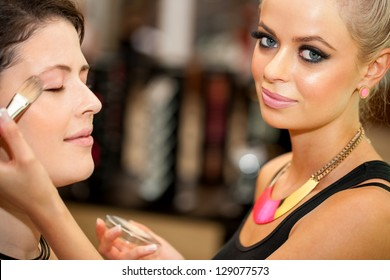 Close up portrait of attractive female make up artist at work.