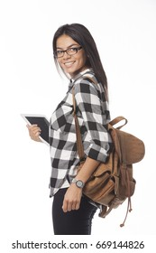 Close up portrait of attractive female student in glasses and  plaid shirt with tablet computer and backpack. Looking back over her shoulder isolated on white