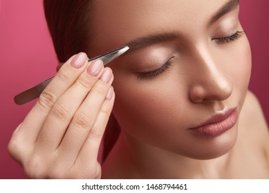 Close up portrait of attractive girl with closed eyes receiving correction of eyebrows form. Isolated on pink background