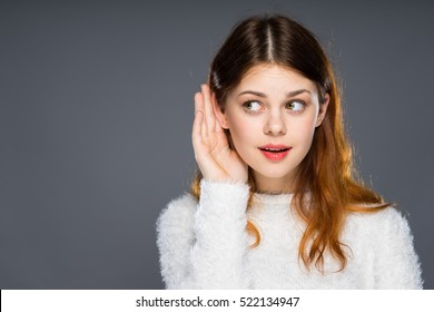 Close up portrait of attractive girl with red lips. Gossip girl eavesdropping with hand to ear. Woman overhearing listening to rumors. Spying and secret concept.isolated over dark background.