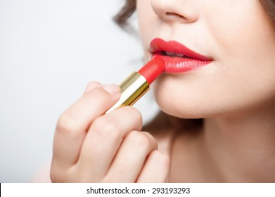 Close up portrait of attractive girl rouging her lips. She is holding red lipstick. Her mouth is gently open. Isolated on grey background