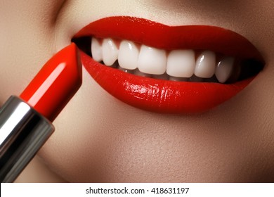 Close up portrait of attractive girl rouging her lips. She is holding red lipstick
