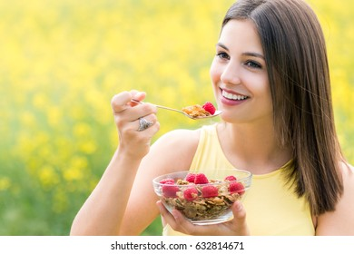 Close up portrait of attractive healthy young woman eating crispy whole grain cereal breakfast outdoors.Girl holding bowl with cereal and spoon against colorful yellow flower field.