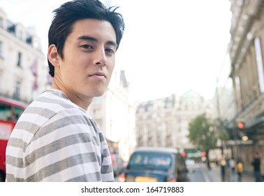 Close up portrait of an attractive Japanese tourist man visiting the city of London turning while standing on a classic architecture grand street with space and sunny skies, outdoors.