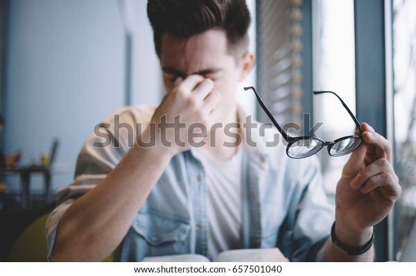 Close up portrait of an attractive man with eyeglasses. Poor young guy has eyesight problems. He is rubbing his nose and eyes because of weariness