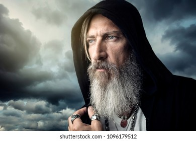 Close up portrait from an attractive man with a grey beard and a hood in front of a dramatic sky