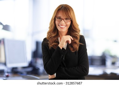 Close- up portrait of attractive middle age businesswoman standing at office while looking at camera and smiling.