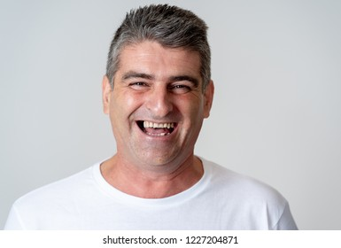 Close up portrait of an attractive middle aged man having fun and looking happy joyful smiling and laughing at the camera in human emotions facial expressions happiness and feelings