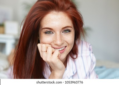 Close up portrait of attractive red haired young Caucasian woman with green eyes and perfect freckled skin spending morning in bed, wearing pajamas. Beauty, youth, leisure, people and lifestyle