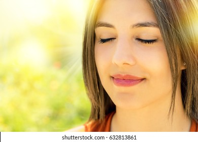 Close up portrait of attractive relaxed young woman meditating outdoors.Girl with eyes closed against bright colorful outdoor background.