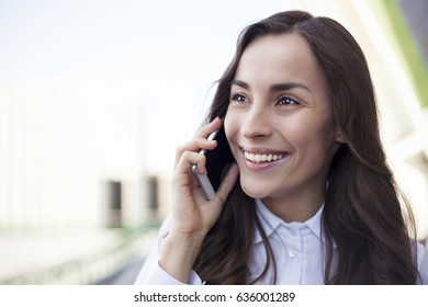 Close up portrait of Attractive smiling brunette businesswoman talking on mobile phone with client.