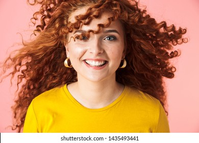 Close up portrait of an attractive smiling happy young woman with long curly red hair standing isolated over pink background