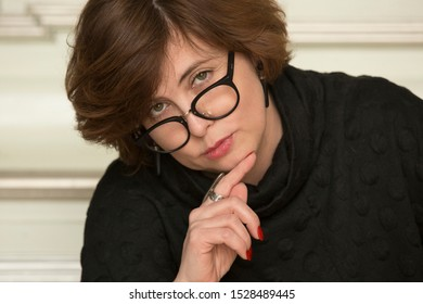 Close up portrait of attractive stylish charming confident, pensive, serious woman wearing glasses. Active beautiful middle-aged businesswoman looking into camera.