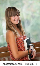 Close up portrait of attractive teenage girl with reading book.