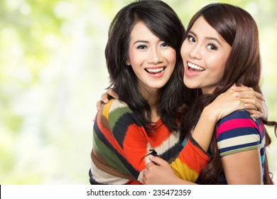 close up portrait of attractive two teenage girls hugging each other