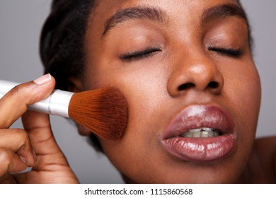 Close up portrait of attractive woman applying makeup with brush for beautiful complexion