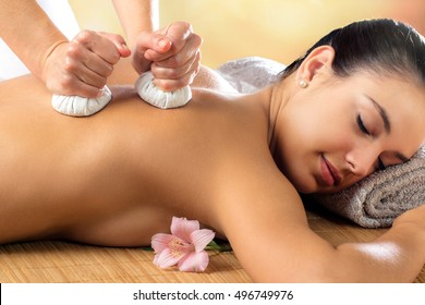 Close up portrait of attractive woman enjoying aromatic ayurveda pinda massage on back and shoulder.