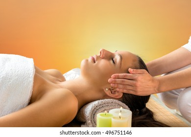 Close up portrait of attractive woman having alternative therapy treatment. Therapist holding hands next to head.