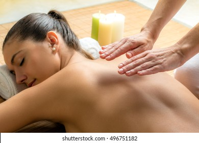 Close up portrait of attractive woman receiving alternative therapy on spine.Therapist working on energy channels on female back.