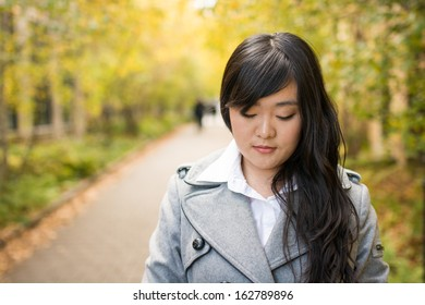 Close up portrait of attractive young girl alone on a road looking depressed