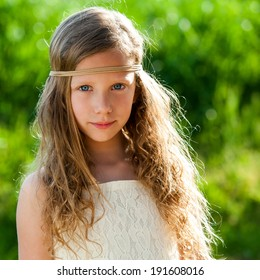 Close up portrait of attractive young girl wearing ribbon headband outdoors.