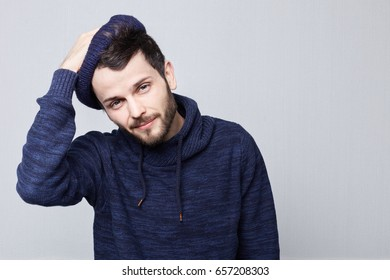 Close up portrait of attractive young male with thick beard and charming blue eyes wearing stylish clothing, looking at camera with flirty smile, keeping hands on his head. People and lifestyle