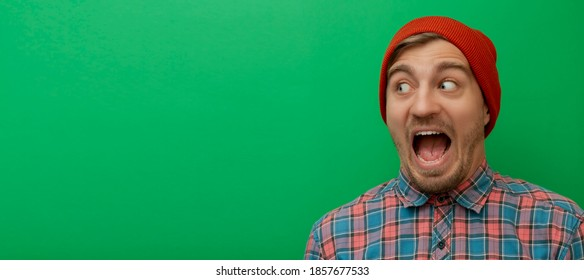 Close up portrait of attractive young model isolated on green background. Young man is surprised.  Hipster