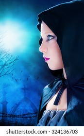 Close up portrait of attractive young mysterious Gothic girl wearing black hood.Graveyard with full moon in background.