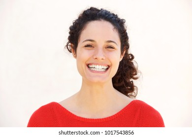Close up portrait of attractive  young woman smiling against isolated white background