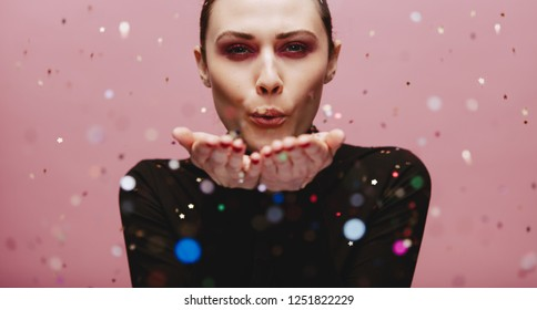 Close up portrait of attractive young woman blowing sparkles. Caucasian female model blowing glitters over pink background.