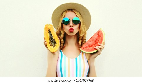 close up portrait of attractive young woman with fruits slice of watermelon and papaya blowing red lips sending sweet air kiss wearing straw hat, sunglasses on white background