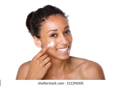 Close up portrait of an attractive young woman applying cream on face