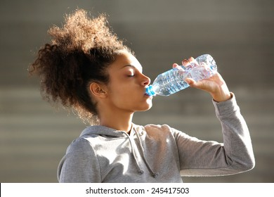 Close up portrait of an attractive young woman drinking water from bottle