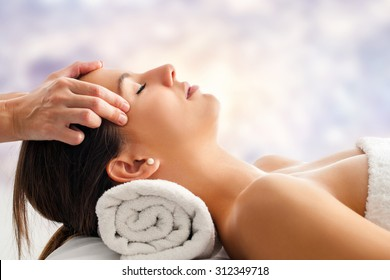 Close up portrait of attractive young woman having relaxing facial massage. Therapist doing head  massage  head against bright colorful background.