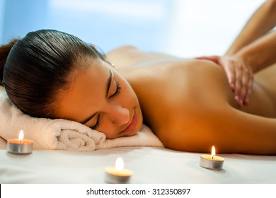 Close up portrait of attractive young woman having relaxing body spa treatment in dim candle light. Therapist in background massaging back.