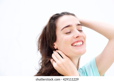 Close up portrait of attractive young woman smiling  with hands in hair