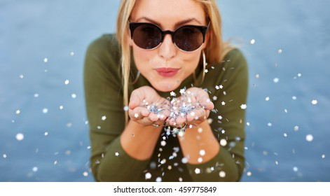 Close up portrait of attractive young woman blowing glitters. Caucasian Female model having fun over blue background.