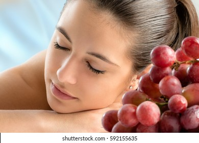Close up portrait of attractive young woman relaxing with eyes closed in spa.Out of focus bunch of grapes in foreground.
