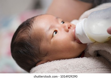 Close up portrait of a baby bottle feeding on milk formula.