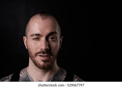 Close up portrait of bald man with tattoo. Positive person wink to the camera. Brutal boy on neutral black background with copy space for text or goods.