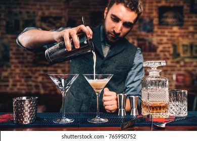 close up Portrait of barman pouring fancy cocktail in bar at party. Manhattan cocktail beverage in nightclub