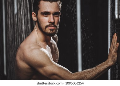 close up portrait of bearded black-haired man looking at the camera while taking a shower