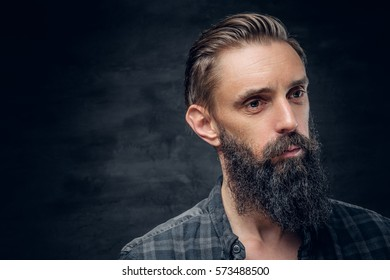 Close up portrait of bearded male with long hair over dark background.