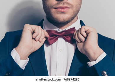 Close up portrait - bearded man ties a bowtie at the collar, correcting red bow on his white shirt over grey background