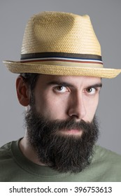 Close up portrait of bearded man wearing straw hat with intense look at camera. Headshot over gray studio background.