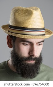 Close up portrait of bearded man wearing straw hat looking down. Headshot over gray studio background.