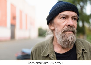 Close up portrait of beardy old man outdoors. Homeless man with sad look.