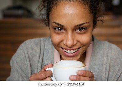 Close up portrait of a beautiful african american woman smiling with cup of a coffee