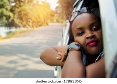 Close up portrait Beautiful African woman  She sits relaxed, leaning near the car door, on the road and looking at the camera with peace of mind.